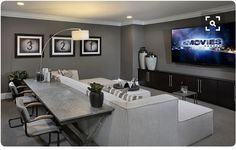 Media room area. Large comfy sectional couch, media cabinets, large tv, sofa table with bar stools for added seating.
