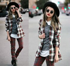 Plaid top with a colored tank top underneath with black leggings and black boots. with hair slightly curled