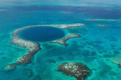 An aerial view of the coral reef and deep cave that make up the famous diving spot of the Blue Hole in the Caribbean Sea, off the coast of Belize. Credit: Tami Freed/Shutterstock