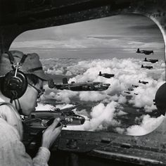 Japanese officer seated at aircraft window and talking on radio, with flight of…