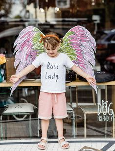 Little girl wearing a Boss Lady t-shirt in front of window with painted wings at Holly & Co Girls Wear, Dog Friends, Boss Lady, Little Girls, Entrepreneur, Wings, Ballet Skirt, T Shirts For Women, School