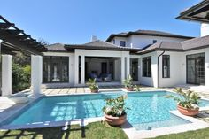 The Sarasota, Fla., home features a British West Indies architecture style with elegant gray roofing and soft white stucco exterior. Pavers are laid in a grid and softened with grass to create an elegant yet functional surround around the pool.