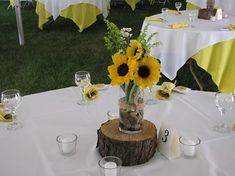 Sunflower and wood centerpieces. (: Simple and pretty. Easy and cheap DIY centerpiece vase and rocks are from Dollar Tree. I placed a bulk order of sunflowers, with a little bit of baby's breath and some lavender wildflowers to accent from the florist. We set it all up the morning of the wedding. Pretty simple if you have help. I suggest delegating though its a stressful day, so delegate delegate delegate! :)