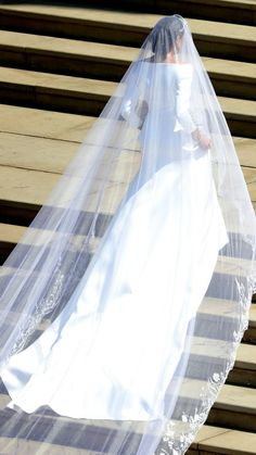 While with a more modern recognition value may have seemed likely, Meghan Markle oozed timeless elegance through simplicity when she walked up the stairs of St. George's Chapel entirely on her own in a collar-neck satin gown designed by Clare Waight Keller, Givenchy's new and first female head designer. The radiant bride of England's Prince Harry accessorized the gown's heavy fabric with a stunning 6 meter-long veil and a sparkling tiara of Queen Mary in her dark upswept hair. Windsor, May…