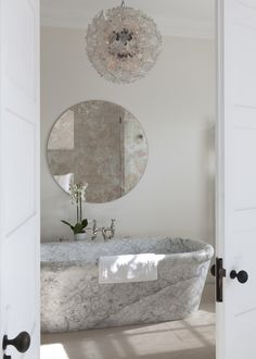 looking through floor to ceiling doors into a white marble bathroom with freestanding bath.
