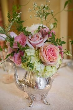 Vintage silver teapot steps in to take on the role of vase! Roses and hydraneas look lovely against the silver.