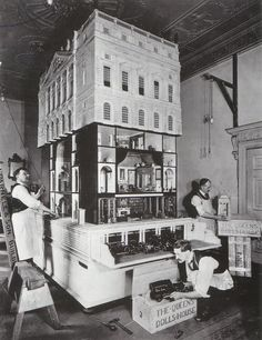 Prepare yourself for doll house squealing. I've just come across the most ornate doll house I've ever seen: Queen Mary's doll house, as the box above so eloquently states. Completed in 1924, it was made to a scale of 1:12, is over three feet tall, and contains models of tons of products made by companies of the time. (Did I mention that Queen Mary was an adult at the time of this doll house's creation?) Many of the items in the house are 1/12 replicas of items in Windsor Castle, and tons of…
