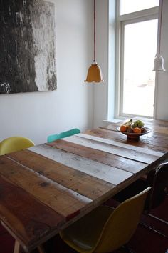 Mesa de madeira de demolição, mix de cadeiras em tons pastéis, luminárias coloridas em tulipas de vidro.