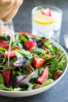 Strawberry Spinach Salad - a photo of dressing being poured onto a salad topped with strawberries and pecans with a glass in the background - click photo for full written recipe