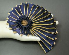This fun cocarde is made with beautiful vintage ribbon in dark blue with gold metallic edges. At the center is a smaller dark blue cocarde and a vintage goldtone mirror back button. Measures 4.75X6.75, the back is unfinished buckram.       .
