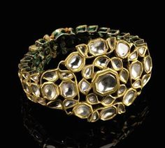 A Mughal diamond & enamel gold bracelet, India, late 18th-19th century. The central open work flowerhead set with table-cut diamonds, the bracelet formed of three rows of diamonds, the reverse with gold motifs on a green enameled ground.