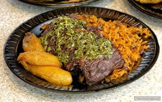 "The ""Churrasco"" platter features a skirt steak marinated in house-made chimichurri, then grilled over an open flame! Sides include a ""dirty"" rice mix and plantains (available a couple different ways). The Churrasco platter is listed on the boards as being $13.00 (2017)."