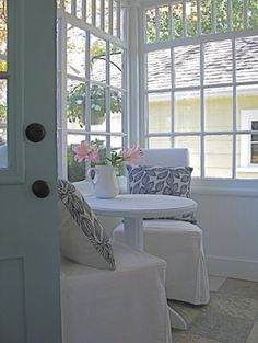Inexpensive way to create a soft setting on a tiny porch - just slipcovers on simple chairs and a pedestal table