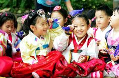 Korean grade school students dressed in traditional Korean Clothes are being taught the traditions & customs for Chuseok.
