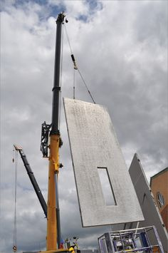 A photo of two cranes installing precast concrete panels at a construction site.
