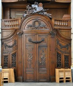 La porte d'entrée de la chapelle Notre dame à Besançon avec ses boiseries Elle est datée de la fin du XVIIIe siècle, mais sans certitude. Son bois sculpté représente les instruments de la liturgie.