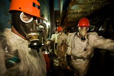 Workers, wearing respirators and plastic suits for protection, pause briefly on their way to drill holes for support rods inside the sarcophagus. It is hazardous work: radiation is so high that they constantly need to monitor their Geiger counters and dosimeters, and they are allowed only one 15-minute stay in this space per day. Chernobyl Nuclear Power Plant, Ukraine, 2005