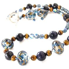 This blue and gold necklace set with tigers eye and art glass creates an abstract animal print effect. Get this chic and artful ensemble from our online shop.