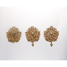 PAIR OF DIAMOND 'KERONGSANG RANTAI' BROOCHES Modelled as a single flower head, the circular plaques each centring on a cushion-shaped old mine-cut diamond weighing approximately 2.05 and 2.30 carats respectively, surrounded by bird, bat and bee motifs encrusted throughout with rose-cut diamonds, suspending a diamond-set heart, the diamonds altogether weighing approximately 4.00 carats, one diamond deficient, completed by two detachable diamond-set floral chains, loop deficient, mounted in 18…