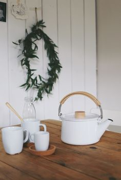 white enamel kettle and Ikea cups, green wreath, white boarded walls in kitchen. Me&Orla
