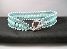 Seadbeady, Turquoise White Beaded Malaysian Jade Bracelet. The bracelet is made in herringbone stitch in the colours turquoise and white with Turquoise Malaysian Jade beads. This bracelet looks very chic and is excellently suited for festive occasions. The lenght is 20 cm clasp included.  Made with Miyuki seed beads. Finished with silvercoloured T clasp.  All my jewelry has been made by hand with needle and special thread for jewelry.  Would you like to have a jewel designed for you…