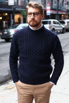 Nail off-duty dressing with this combination of a navy cable knit sweater and tan chinos.   Shop this look on Lookastic: https://lookastic.com/men/looks/navy-cable-sweater-light-blue-long-sleeve-shirt-khaki-chinos/7620   — Light Blue Long Sleeve Shirt  — Navy Cable Sweater  — Khaki Chinos