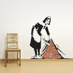 Banksy Sweep It Under Wall Decals beside chair