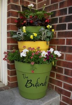 This is a simple inexpensive project to jazz up your front door.. Plastic pots painted the color of your choice. You can use clay pots, but they are more $. spray paint and then add soil, stack your pots, flowers and your family name! via~ Backyard Diva  www.backyarddiva.ca