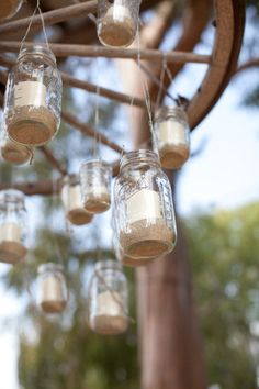 hanging mason jars filled with sand and candles