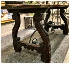Spanish Baroque Refectory table, 18th century, walnut and wrought iron, thick 2 board top with carved ends and trestle from base and scrolled wrought iron double stretchers from a major Virginia Estate.  $10,000.  Gaslamp Antiques Too, booth T360H6353.