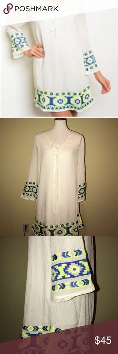 White Dress w Neon Embroidered hem and Sleeves Brand New boho style white dress with yellow and blue neon embroidery at hem and Sleeves. Dress is fully lined. Has a tie up Neckline. Perfect for day to night. Dresses Mini