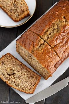 Above view of banana bread with three slices taken. One of the slices is laying flat so the inside of the bread is visible.