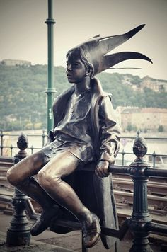 The Little Princess (Kiskirálylány) statue found on the Danube Promenade. This small statue of a young girl, playfully sitting on the Promenade railings, wearing a princess outfit and crown is the creation of Hungarian sculptor, László Marton, who gave this statue to the city in 1972.