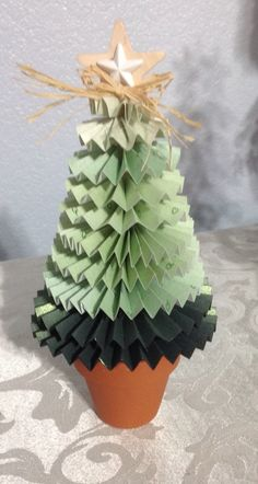 Tree made from scrapbook paper, cut in graduated strips, folded fan style, and glued into a circle. Beginning from largest to smallest, stack circles onto a dowel and place in a stand of your choice.
