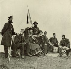 Woman sitting with a group of soldiers.