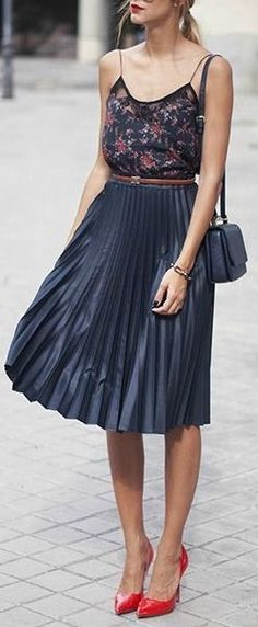 Cute printed cami with navy pleated skirt and red heels.