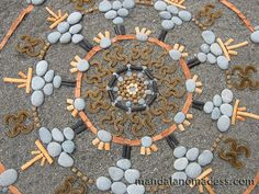 Mandala Art Medium:  ~~grey stone, gold pebbles, bull kelp rope, eucalyptus bark, grey stone, kelp body, bleached seaweed, and black seaweed stipe on dark sand canvas~~