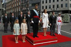 Spain's newly crowned King Felipe VI listens to the national anthem next to his wife Spain's Queen Letizia, their daughters