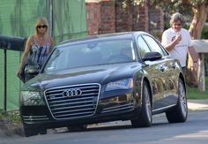 Goldie Hawn & Kurt Russell walking to their black Audi A8