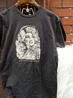 """Who doesn't need a t-shirt starring the queen of country music?  Add one of her favorite quotes """"It's hard to be a diamond in a rhinestone world,"""" and this design is almost too good to be true! Printed on super soft Next Level fashion fitting tees in a dark grey heather color. This design was drawn by local Artist/Mammoth Printshop employee - Britt Cherry."""