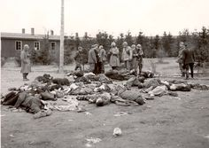 Ohrdruf, Germany, American soldiers and liberated prisoners standing near prisoners' dead bodies, during the camp's liberation.