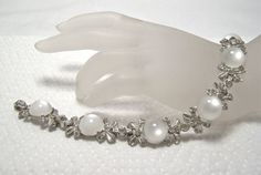 Silver tone bracelet with domed white moonglow cabs and pave ribbons