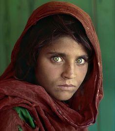 """Sharbat Gula tinha 12 anos quando foi fotografada durante uma reportagem da """"National Geographic"""" sobre a ocupação soviética no Afeganistão. Se tornou uma das fotografias mais conhecidas do mundo. Em 2002, o fotógrafo Steve McCurry, autor da fotografia, reencontrou Gula, então, com 30 anos, numa região remota do Afeganistão. Ela não tinha a menor ideia do impacto que sua foto causou na civilização ocidental. Fotografia: Steve McCurry"""