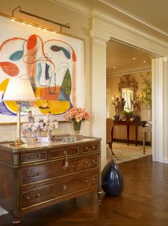 Beautiful antique dresser with bold and colorful abstract art creates a warm and inviting entrance.