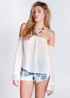 """Summery off-the-shoulder peasant top featuring pretty lace detailing at the sleeves.  100% Polyester 22"""" length Model is wearing size S"""