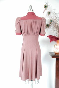 Vintage late 1930s dress is my favorite day dress of the year. I have hoarded it for nearly two years because really, if this were my size it would be in the permanent collection forever! Made of a soft rayon wool blend, the 1938 silhouette is perfect and flattering, with pleated shoulders at the sleeves, a fitted midwaist and swingy pleated skirt. Color blocking of a soft heathered plum coordinates with the plum and grey striping. The collar, cuffs, and pocket accents are solid, along with…
