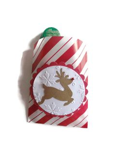 Make your party magical with these adorable reindeer mini paper bags. You get 12 bags per set. Each red and white striped bag has a reindeer complete with his red rhinestone nose. The reindeer is adhered to an embossed circle with a snowflake print. There is a red scallop framing each image. A great favor bag which holds 4 mini reeses cups. These are also the perfect size for a gift card. What a lovely way to give your guests a special favor to take home.  12 reindeer bags measures 3 x 4…