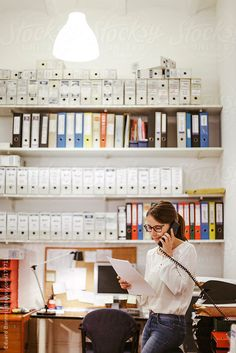 Businesswoman at phone working in her office. by Eduard Bonnin #stocksy #realstock