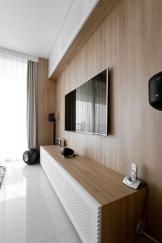 Home theater com aparador baixo em madeira e portas ripadas brancas