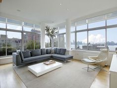 Love the wall of windows and the grey sectional!